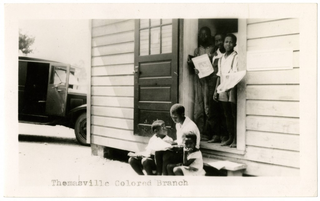 AfricanAmerican_children_hold_books_in_doorway_of