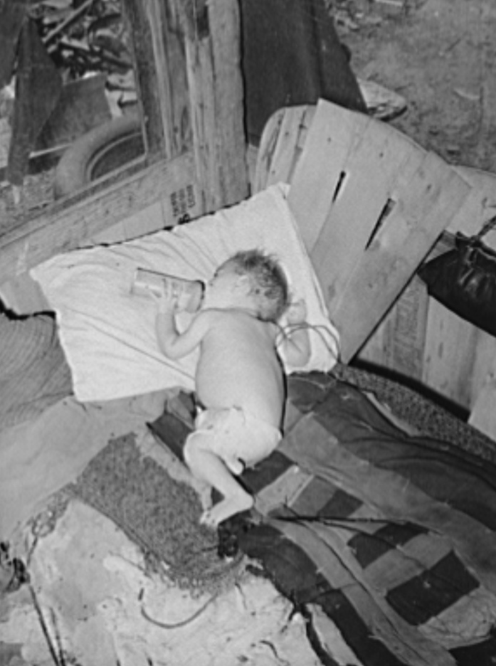 Baby with his bottle in shack home near Mays Avenue camp. Oklahoma City,
