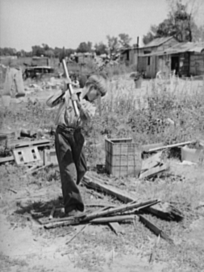 Boy living in Mays Avenue camp, Oklahoma City, Oklahoma, chopping wood