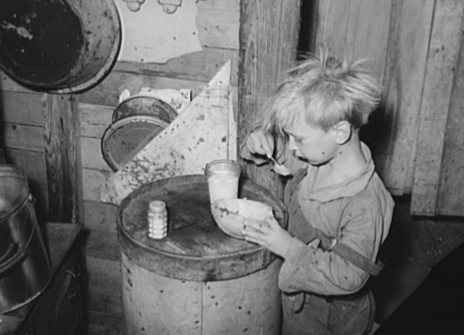 Child in Mays Avenue camp, Oklahoma City, Oklahoma, eating an overripe canteloupe found in market