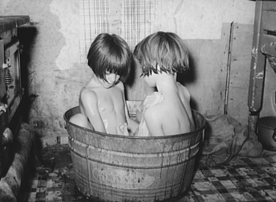 Children taking bath in their home in community camp. Oklahoma City, Oklahoma2