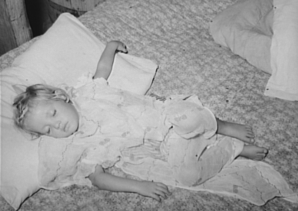 Daughter of water peddler in community camp, Oklahoma City, Oklahoma, asleep. She is covered with old curtain to protect her from flies