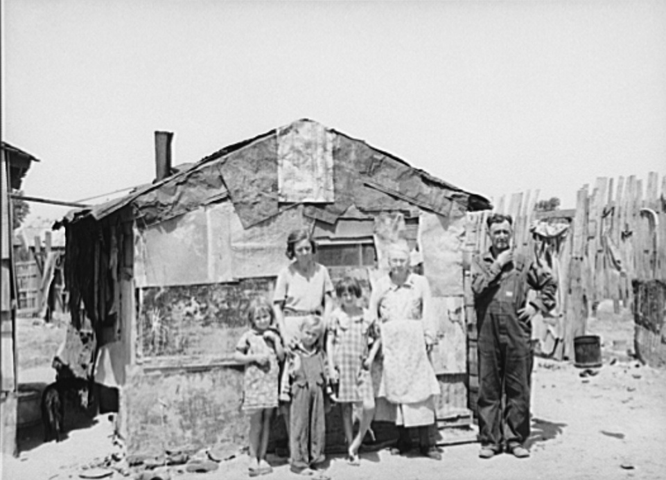 Family in front of shack home, Mays Avenue camp. Oklahoma City, Oklahoma