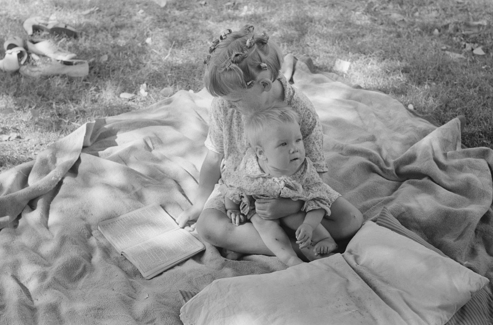 Little girl and her baby brother reading Bible, community camp, Oklahoma City,