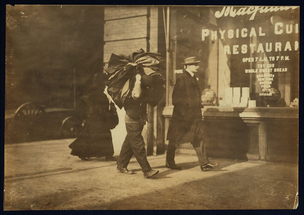 Man carrying bundle of garments. Bleeker St., N.Y. Location New York, New York January 1912