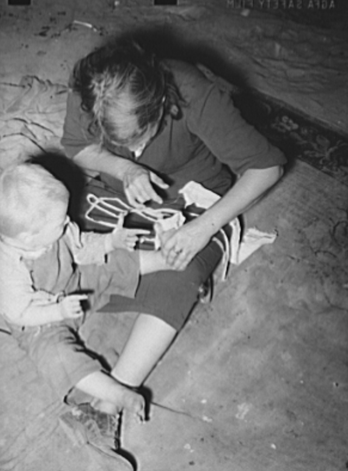 Mother bandaging toe of her son which was cut in debris of Mays Avenue camp. Oklahoma City, Oklahoma