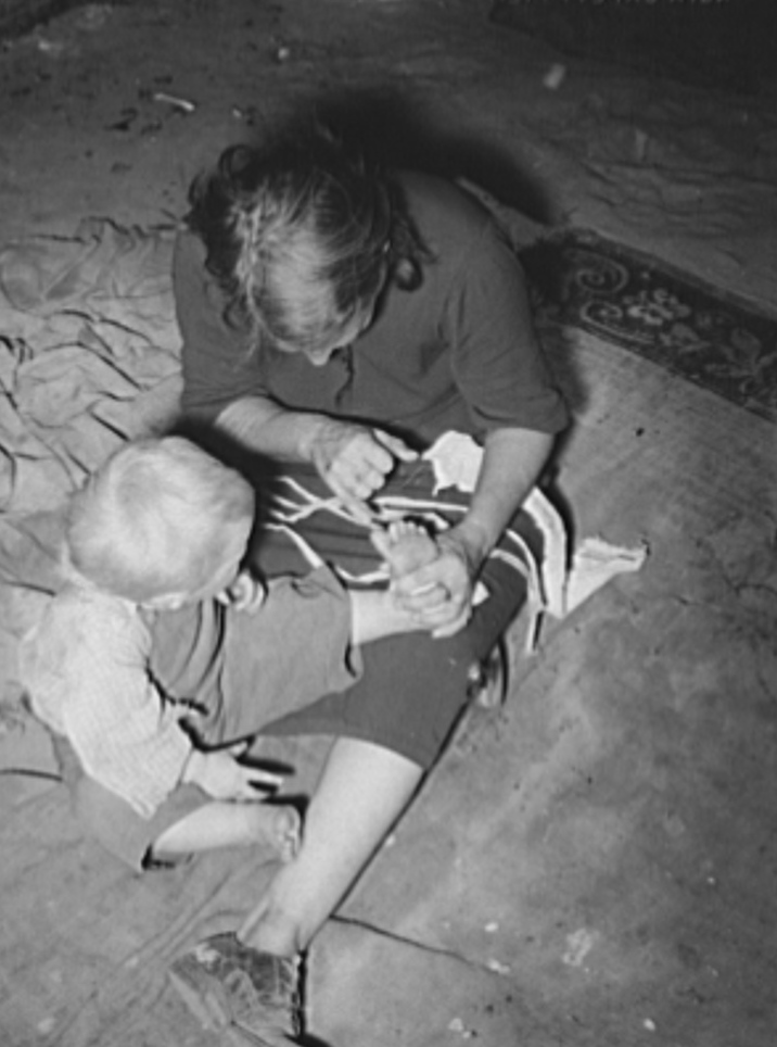 Mother of child pointing to his cut toe, injured while playing in trash and debris of camp. Mays Avenue camp, Oklahoma City, Oklahoma
