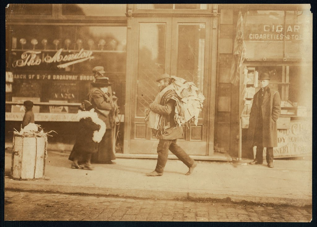 Old man carrying garments, Delaney St., N.Y. Location New York, New York Feb. 1912