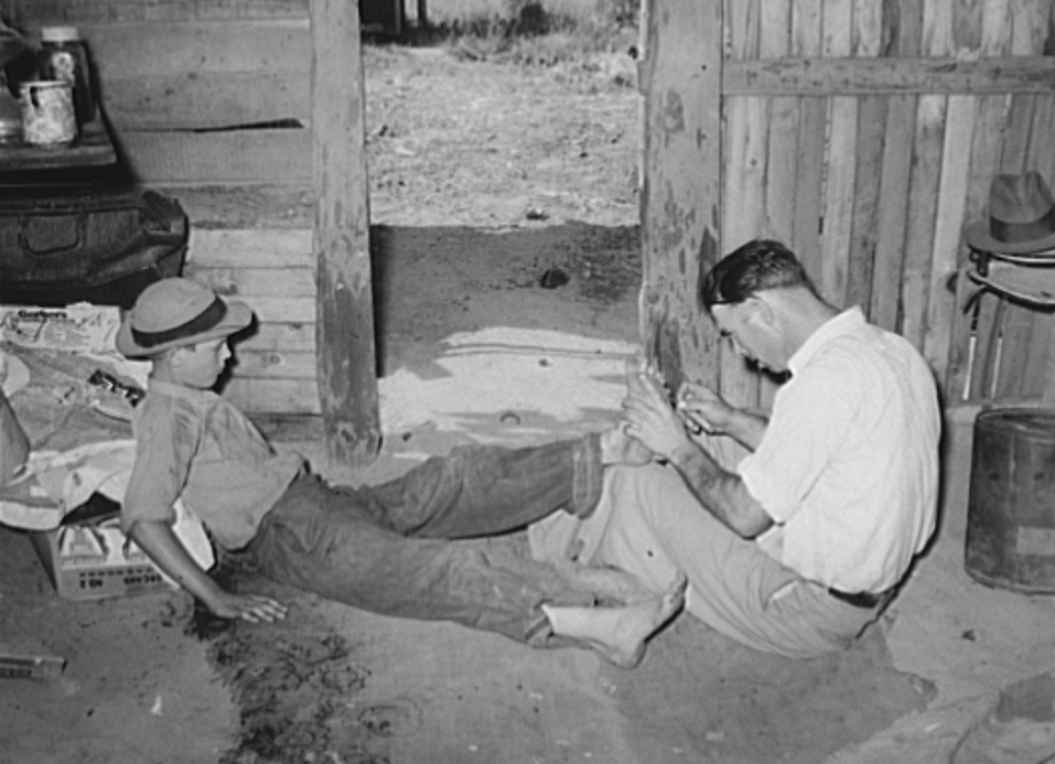 Resident of Mays Avenue camp, Oklahoma City, Oklahoma, taking piece of glass out of boy's foot.