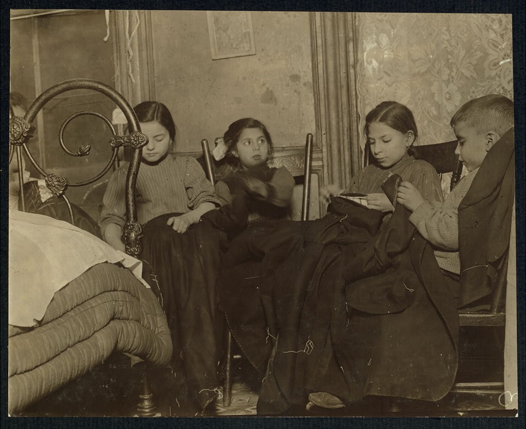 Three girls and a boy working on garments February 1910 Lewis Wickes Hine