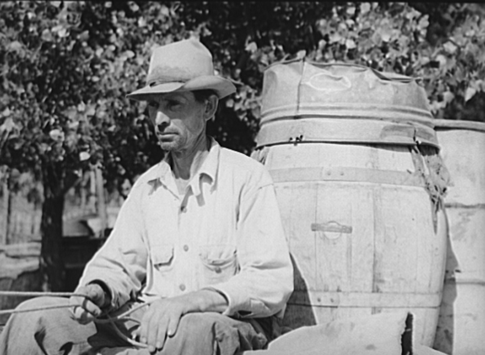 Water peddler in community camp. Oklahoma City, Oklahoma. He is paid fifteen cents a barrel for delivering water to the shack homes