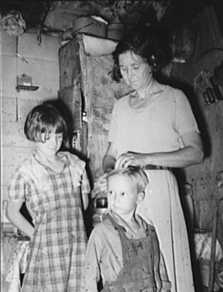 Woman in shack home in community camp. Oklahoma City, Oklahoma. Straightening her son's hair