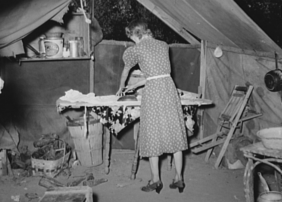 Woman ironing in tent home. Community camp, Oklahoma City, Oklahoma