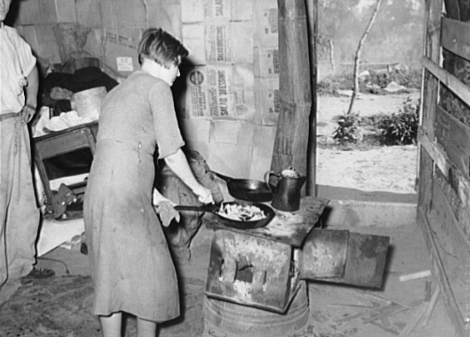 Woman preparing breakfast in shack home. Mays Avenue camp, Oklahoma City