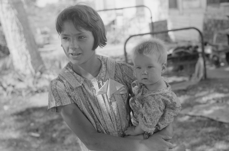 Young girl holding baby brother in her arms, community camp, Oklahoma City