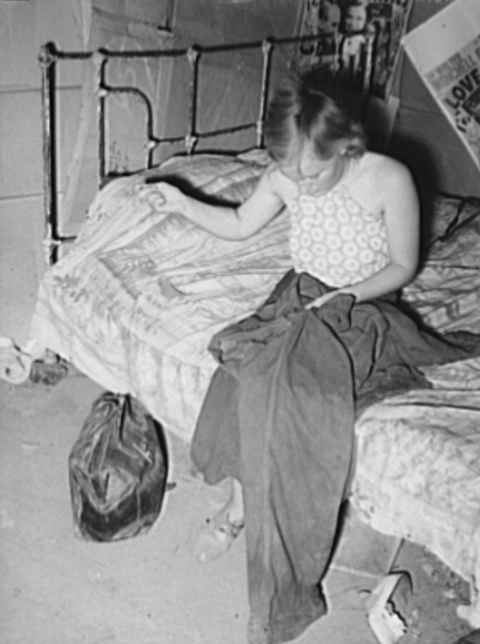 Young married girl living in Mays Avenue camp patching her husband's overalls.