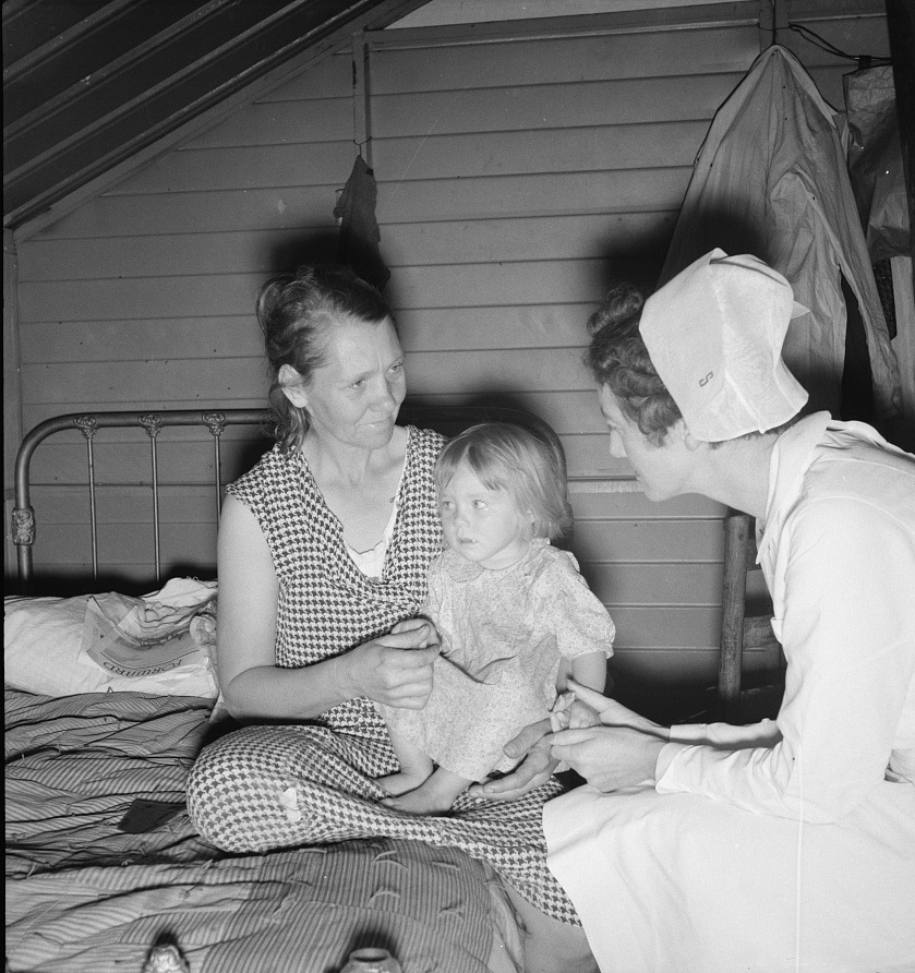 Farm Security Administration (FSA) camp. Farmersville, California. Resident nurse interviews mother and examines sick baby 1939