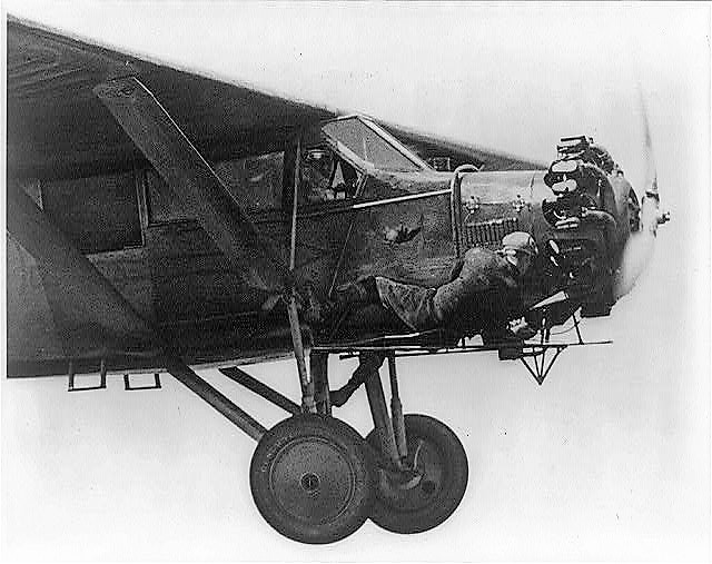 Photograph shows Kenneth Hunter lying down out on the cat-walk; his brother John can be seen flying the plane 1930 (Underwood and Underwood Library of Congress) (2)
